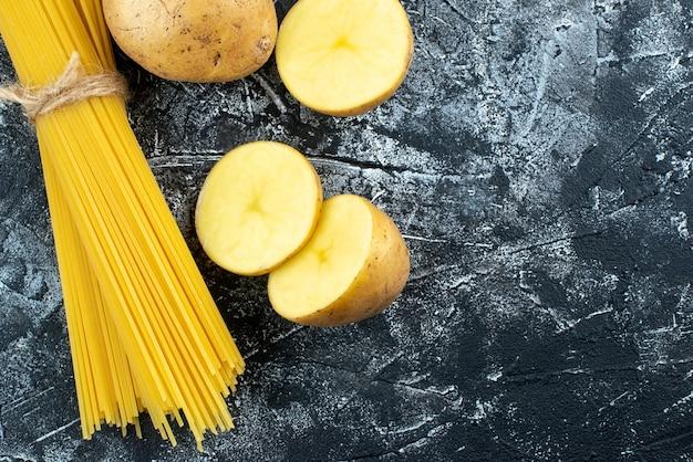 Macarrão longo cru com batatas em um fundo cinza claro.