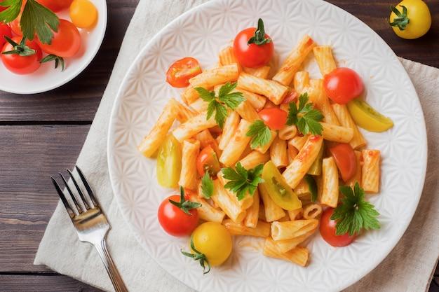Macarrão, macarrão com molho de tomate e queijo em um prato sobre uma mesa de madeira