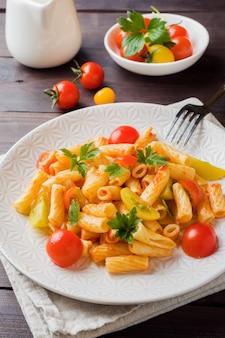 Macarrão, macarrão em molho de tomate e queijo em um prato sobre uma mesa de madeira