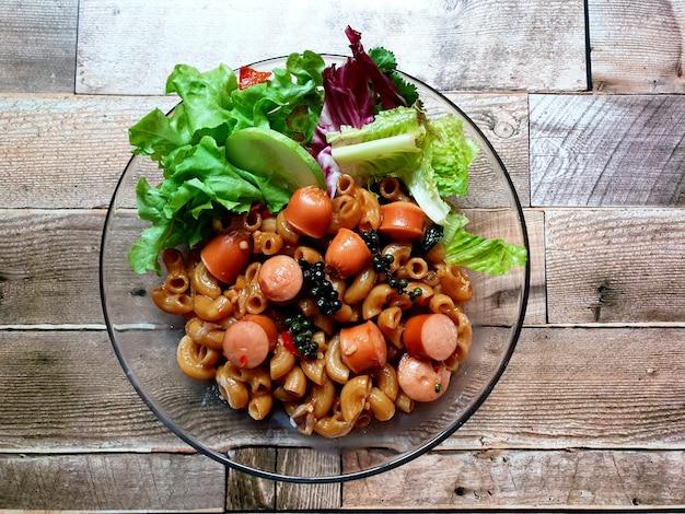 Macarrão mexido com linguiça e legumes em uma mesa de madeira
