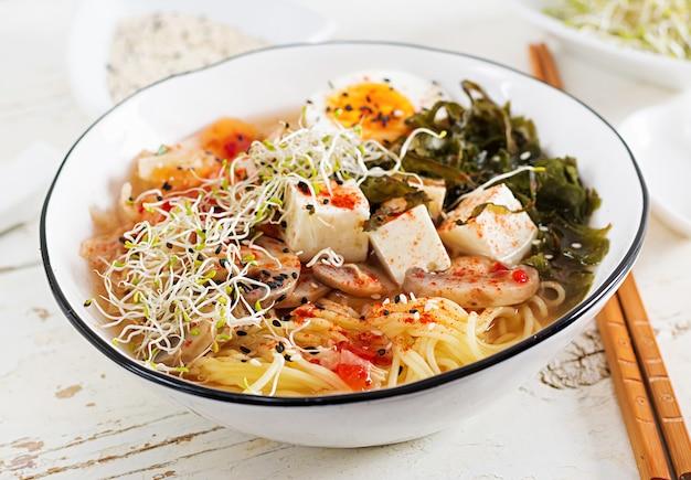 Macarrão miso com repolho kimchi, algas, ovos, cogumelos e queijo tofu em tigela na mesa de madeira branca