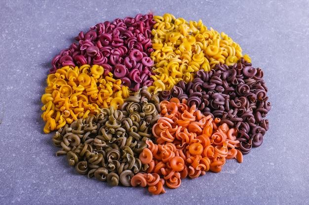 Macarrão multicolorido de forma incomum com corantes vegetais naturais, forrado em círculo