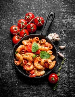 Macarrão na panela com alho, tomate e folhas de hortelã na mesa rústica