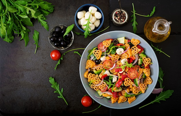 Macarrão na salada coração forma com tomate, pepino, azeitona, mussarela e cebola roxa estilo grego. postura plana. vista do topo
