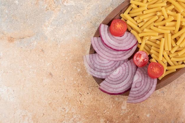 Macarrão não preparado com rodelas de cebola e tomate cereja.