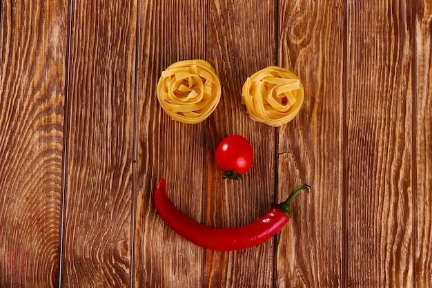 Macarrão no fundo de madeira com tomate e pimenta