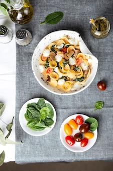 Macarrão orecchiette italiano com espinafre, tomate e mussarela