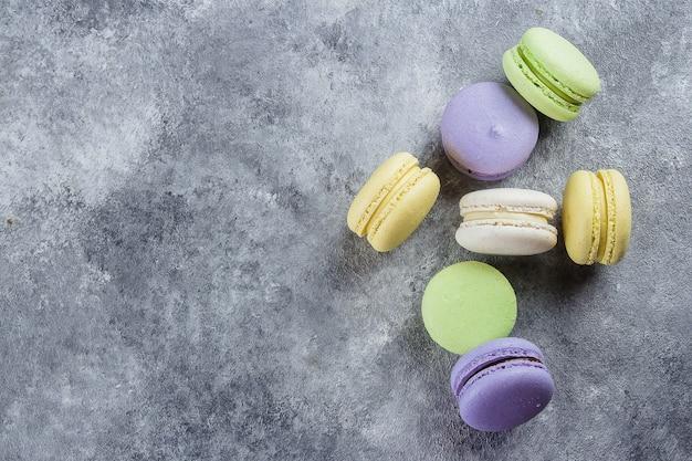 Macarrão ou macaroon colorido do bolo francês ou italiano na tabela concreta com espaço da cópia para o fundo