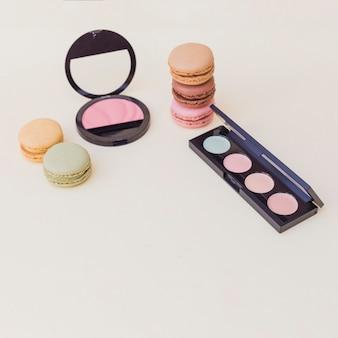 Macarrão; paleta de sombra de olho e blush rosa em fundo colorido