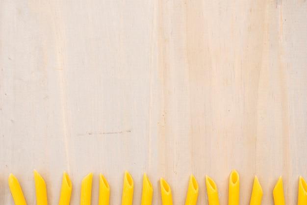 Macarrão penne amarelo cru, disposta em linha no plano de fundo texturizado de madeira