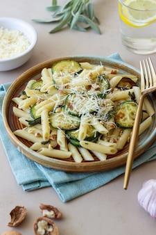 Macarrão penne com abobrinha, sálvia, nozes e queijo parmesão. alimentação saudável. comida vegetariana. comida italiana.