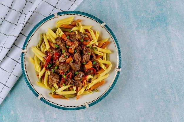 Macarrão penne com guisado de carne com vegetais no prato na mesa azul.