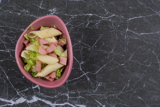 Macarrão penne com linguiça e verduras em uma tigela rosa.
