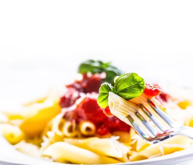 Macarrão penne com molho de tomate à bolonhesa, queijo parmesão e manjericão no garfo
