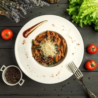 Macarrão penne com molho de tomate, carne e queijo ralado