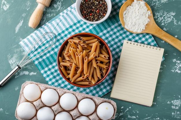 Macarrão penne com ovos, pimenta, amido, batedor, rolo e caderno