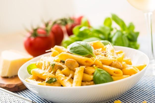 Macarrão penne com pedaços de frango, cogumelos, manjericão, queijo parmesão e vinho branco. comida italiana em chapa branca na mesa da cozinha.