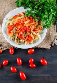 Macarrão penne com salsa, tomate em um prato de madeira e pedaço de saco