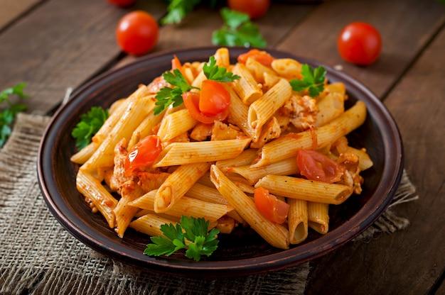 Macarrão penne em molho de tomate com frango e tomate em uma mesa de madeira