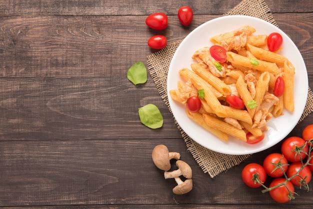 Macarrão penne em molho de tomate com frango em uma mesa de madeira