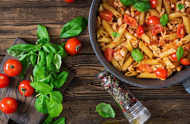 Macarrão penne em molho de tomate com frango, tomate, decorado com manjericão em uma mesa de madeira. comida italiana. massa à bolonhesa. vista do topo. configuração plana
