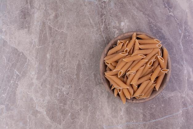 Macarrão penne em uma tigela de madeira rústica em superfície cinza