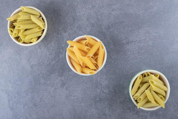 Macarrão penne verde e amarelo cru em tigelas coloridas.