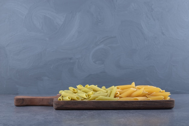 Macarrão penne verde e amarelo cru na placa de madeira.