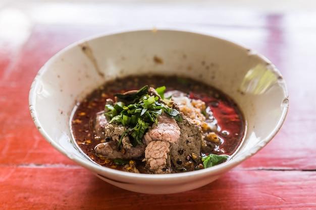 Macarrão picante tailandês com sopa preta close-up