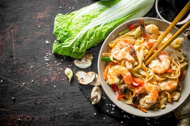 Macarrão quente perfumado com camarão em um prato. em rústico escuro
