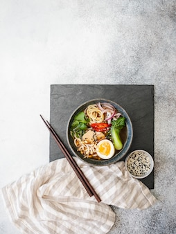 Macarrão ramen asiático com frango, couve pak choi e ovo em uma placa de ardósia preta