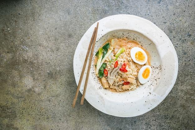 Macarrão ramen japonês com frango, cogumelos shiitake e ovo em uma tigela branca, vista de cima