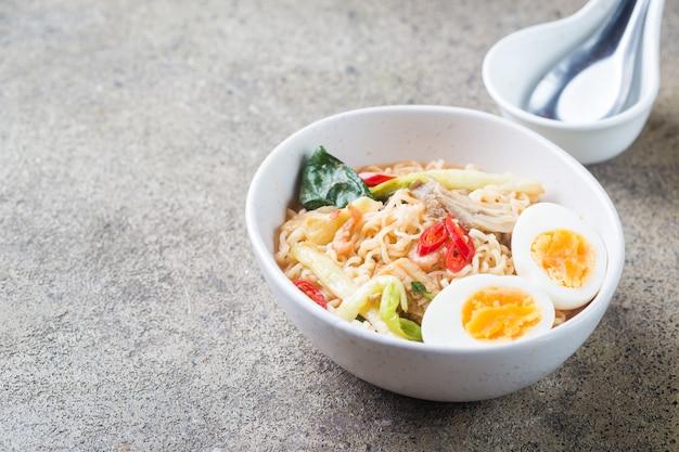 Macarrão ramen japonês com frango, cogumelos shiitake e ovo na tigela branca
