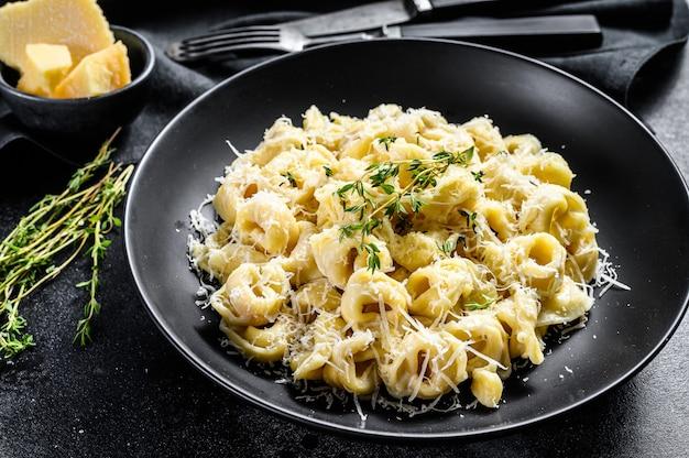 Macarrão ravioli com queijo parmesão em um prato. bolinhos italianos