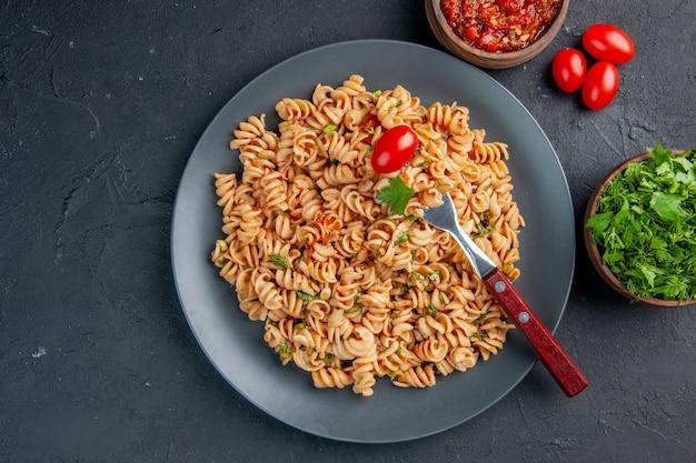 Macarrão rotini com garfo de tomate cereja no prato salsa e molho de tomate em tigelas na superfície escura.