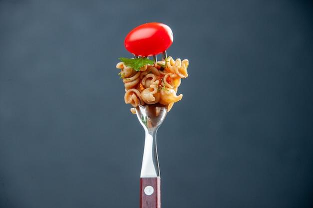 Macarrão rotini de vista frontal com tomate cereja no garfo em superfície cinza isolada com espaço livre