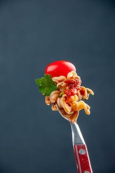 Macarrão rotini de vista frontal com tomate cereja no garfo em superfície escura isolada com espaço de cópia