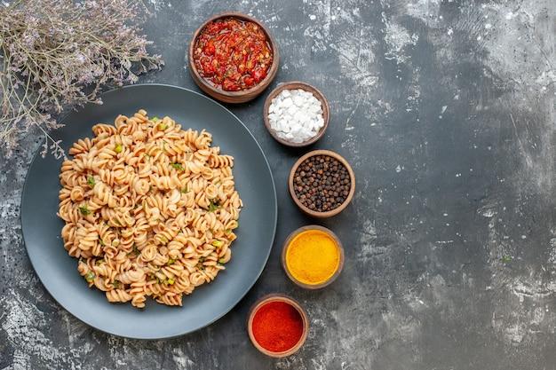 Macarrão rotini em prato redondo, molho de tomate, temperos diferentes em tigelas na mesa escura