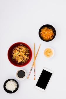 Macarrão saboroso em tigela perto de salada; picles de gengibre; molho de soja e arroz cozido no vapor com telefone móvel no fundo branco