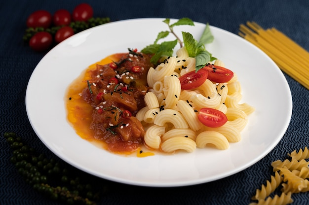 Macarrão salteado com tomate, pimentão, sementes de pimenta e manjericão em um prato branco.