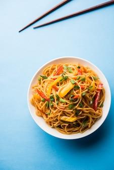 Macarrão schezwan ou macarrão hakka de vegetais ou chow mein são receitas indo-chinesas populares, servidas em uma tigela ou prato com pauzinhos de madeira