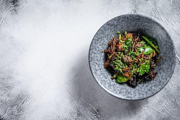 Macarrão soba com carne, cenoura, cebola e pimentão. frite o wok. fundo cinza. vista do topo. copie o espaço