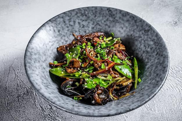 Macarrão soba com carne, cenoura, cebola e pimentão. frite o wok. fundo cinza. vista do topo
