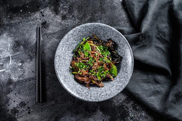Macarrão soba com carne, cenoura, cebola e pimentão. frite o wok. fundo preto. vista do topo