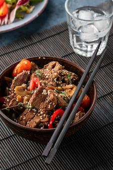 Macarrão soba com carne, cogumelos, tomate cereja e pimentão. cozinha asiática