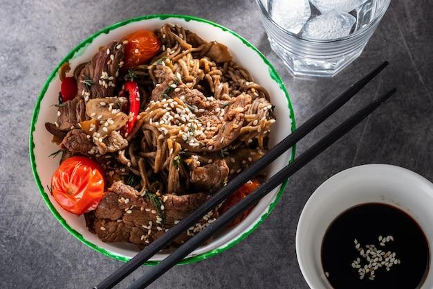 Macarrão soba com carne, cogumelos, tomate cereja e pimentos. cozinha asiática