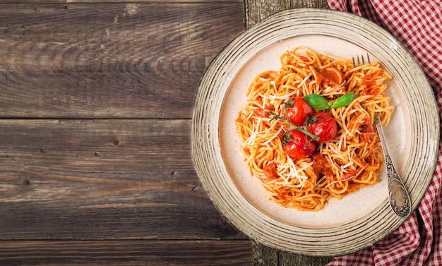 Macarrão spashetti com molho de tomate e cereja de tomate assado na madeira rústica.