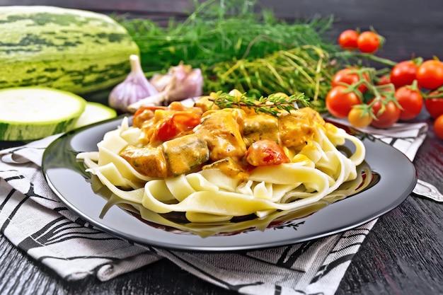 Macarrão tagliatelle com goulash de carne, tomate, abobrinha e tomilho em um prato no guardanapo, alho, erva picante no fundo da placa de madeira