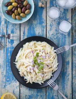 Macarrão tagliatelle em um prato preto perto de um prato de azeitonas em uma mesa de madeira