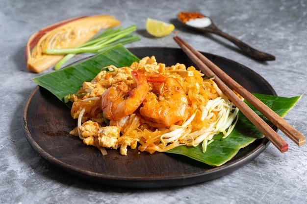 Macarrão tailandês com camarão e legumes close-up em cima da mesa.